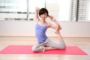 健康と美容対策サプリメントを使用しつつヨガをしている女性。