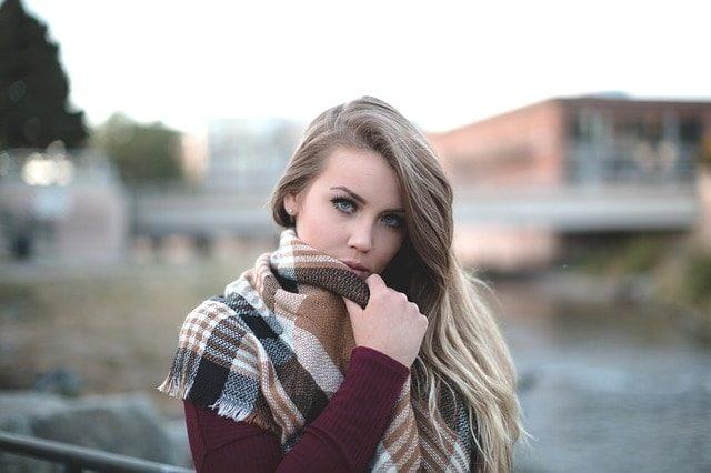 冬にコートを着た金髪女性が寒そうにしている。