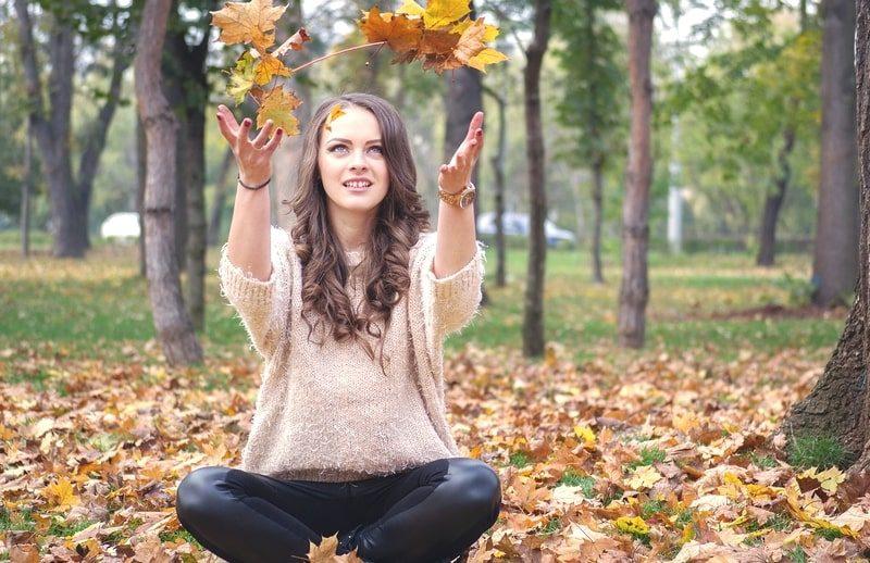 秋の紅葉で落ち葉を舞い上げる美女。